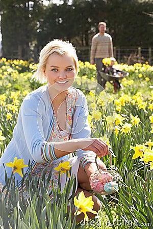 Mulher que esconde ovos de Easter decorados para a caça