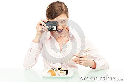 Mulher que fotografa o sushi