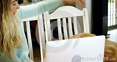 Mulher que joga com seu cão ao usar o portátil 4k video estoque