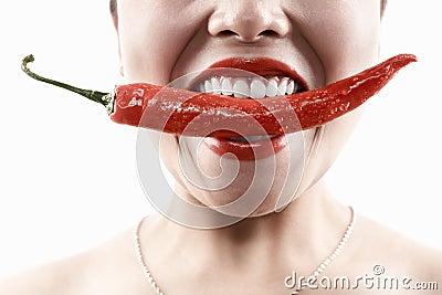 Mulher que prende o pimentão vermelho grande na boca