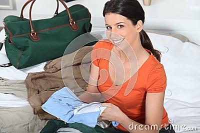 Mulher que prepara a bagagem