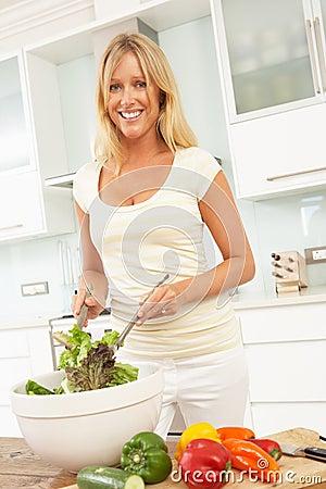 Mulher que prepara a salada na cozinha moderna