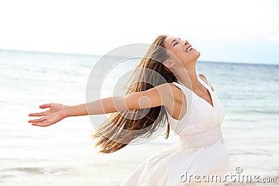 Mulher que relaxa na praia que aprecia a liberdade do verão