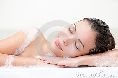 Mulher que relaxa no banho