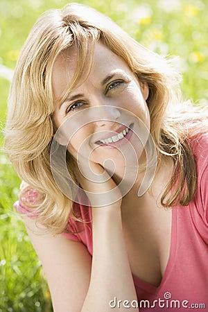 Mulher que senta ao ar livre o sorriso