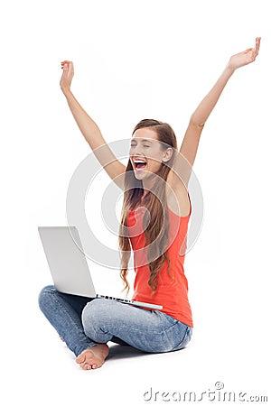 Mulher que senta-se com portátil, braços levantados