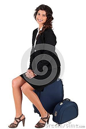 Mulher que senta-se em sua mala de viagem