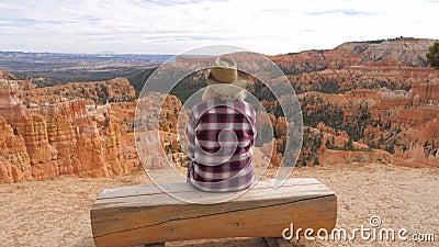 Mulher que senta-se em um banco que olha e que aprecia a vista e as paisagens Bryce Canyon video estoque