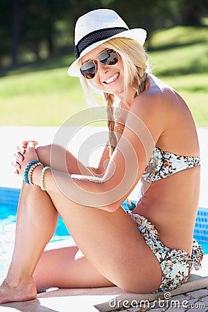 Mulher que senta-se na borda de nadar na associação
