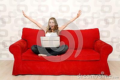 Mulher que senta-se no sofá com portátil