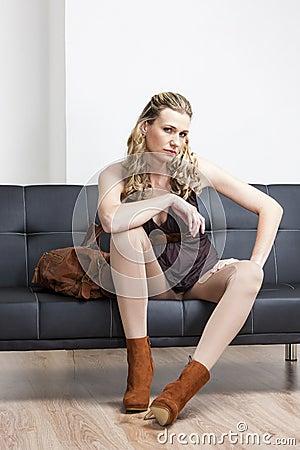 Mulher que senta-se no sofá