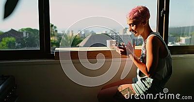Mulher que senta-se perto da janela e que usa o telefone celular 4k vídeos de arquivo
