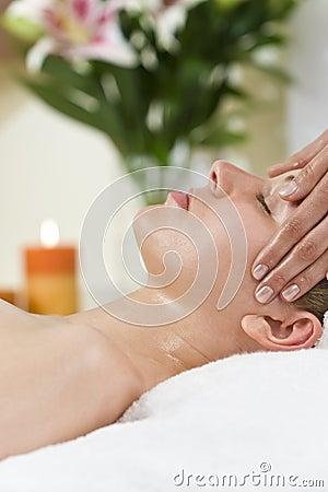 Mulher que tem a massagem principal de relaxamento em termas da saúde