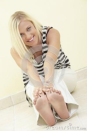 Mulher que toca em seus dedos do pé