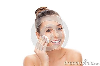 Mulher que usa a almofada de algodão na face