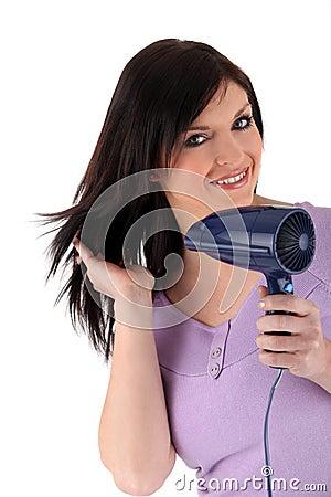 Mulher que usa um hairdryer