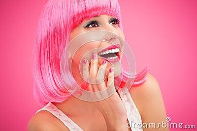 Mulher que veste a peruca cor-de-rosa e o riso