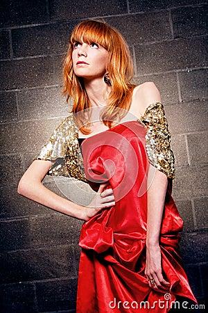 Mulher red-haired elegante em um vestido vermelho do cetim
