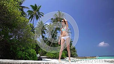 A mulher ruivo delgada anda ao longo de uma praia tropical filme