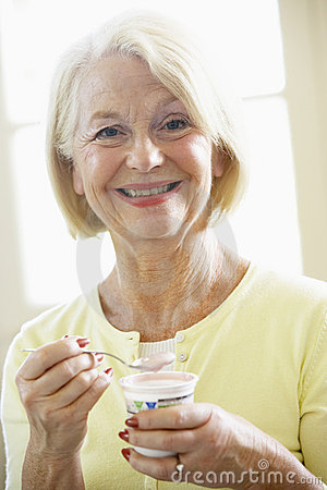 Mulher sênior que come o Yogurt