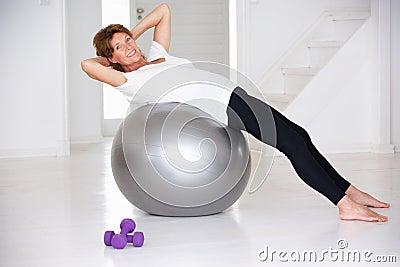 Mulher sênior que usa a esfera da ginástica