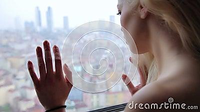 Mulher só que olha através da janela à opinião da cidade vídeos de arquivo