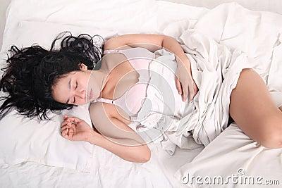 Mulher sensual que dorme na cama
