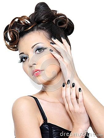 Mulher  sexy  com os pregos creativos do penteado e do preto