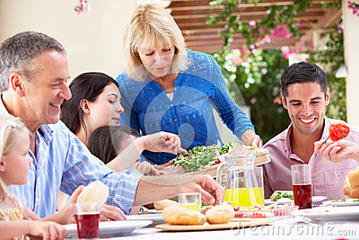Mulher sênior que sere uma refeição da família