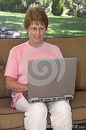 Mulher sênior que usa o computador portátil