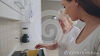 Mulher sorridente ajudando a avó a cozinhar filme