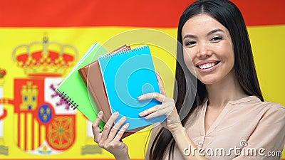 Mulher sorridente mostrando cadernos para câmera, bandeira espanhola, estudo no exterior filme