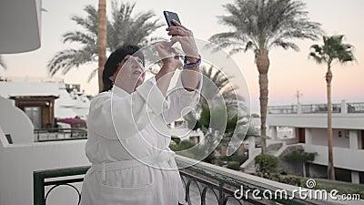 A mulher superior caucasiano toma imagens em um smartphone Deve estar no terraço do hotel em uma veste branca de terry em filme