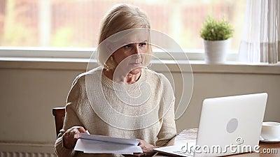 Mulher superior forçada que mantém papéis incomodados com contas domésticas vídeos de arquivo