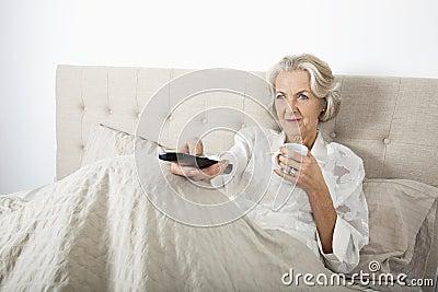 Mulher superior que olha a tevê ao comer o café na cama
