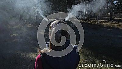 A mulher tem fumaça saindo de sua cabeça e orelhas Atrás da garota está o ritual de cinzeiro de maconha para cerimônias ao ar liv filme