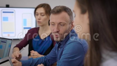 Mulheres e homens estão discutindo no escritório o desenvolvimento de aplicativos móveis durante reuniões de negócios vídeos de arquivo