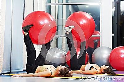 Mulheres no exercício com bola da aptidão