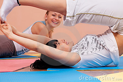 Mulheres novas que fazem exercícios de dobra