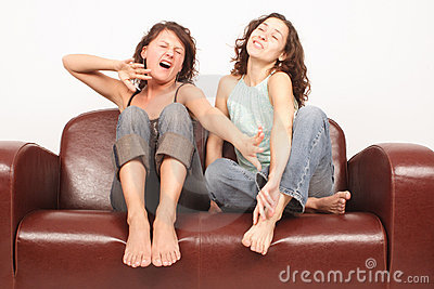 Mulheres novas que sentam-se no revestimento do sofá que presta atenção à tevê