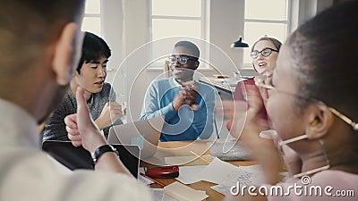 Multi этническая группа на деловой встрече офиса Молодые разнообразные партнеры обсуждают идеи, тогда начинают хлопать и усмехнут акции видеоматериалы