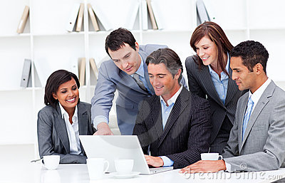 Multi-cultural business team looking at a laptop