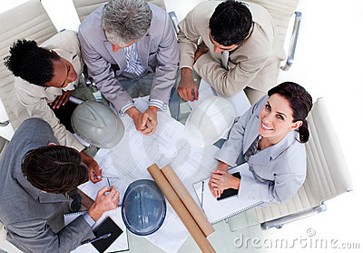 Multi-ethnic architects studying blueprints