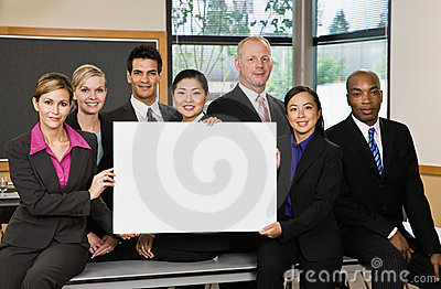 Multi-ethnic co-workers posing with blank sign