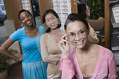 Multi Ethnic Friends Trying On Glasses At Optometrist