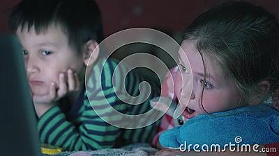 Multi-etnische jongen en wit meisje die op de laag die op het notitieboekje letten in dark liggen 4K stock footage