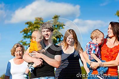 Multi-generation familj på äng i sommar
