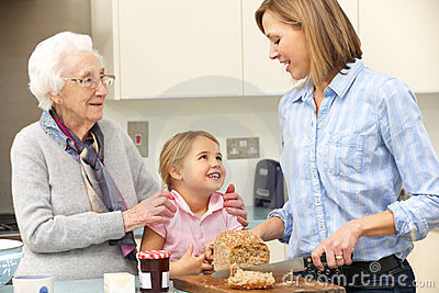 Multi-generation family preparing food in kitchen