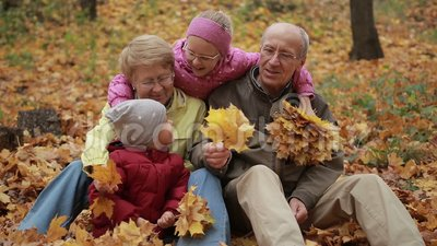Multi generation family relaxing in autumn park stock video footage
