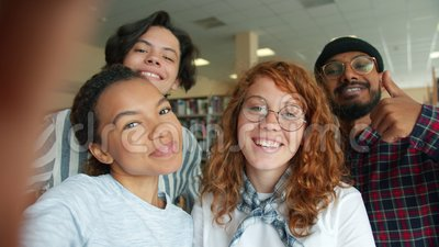 Multi-racial group of young people taking selfie in college library smiling. Multi-racial group of young people students is taking selfie in college library stock video footage